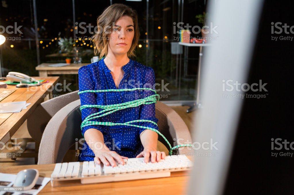 Empresaria atada con la cuerda mientras se trabaja en computadora en su escritorio - foto de stock