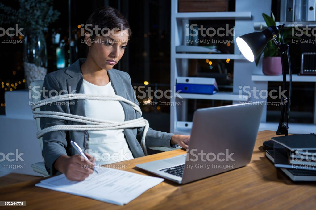 Businesswoman tied with rope while working on laptop at her desk stock photo