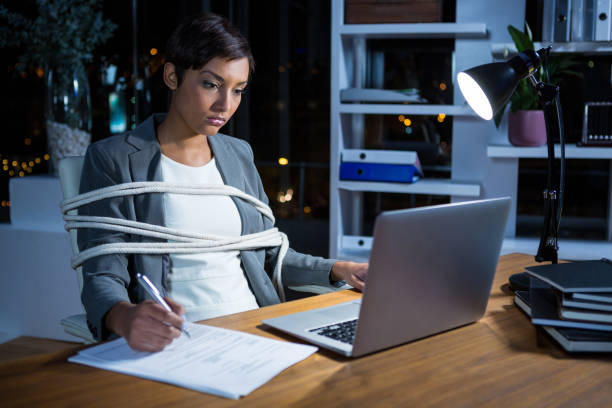 Businesswoman tied with rope while working on laptop at her desk Businesswoman tied with rope while working on laptop at her desk in office at night trap stock pictures, royalty-free photos & images