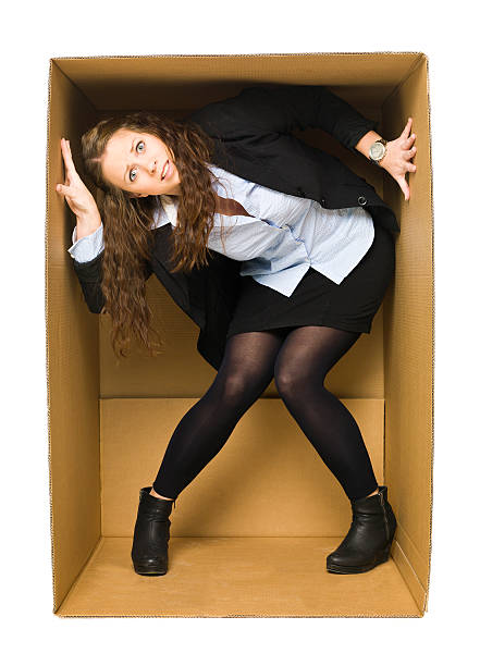 Businesswoman trapped in a cardboard box stock photo