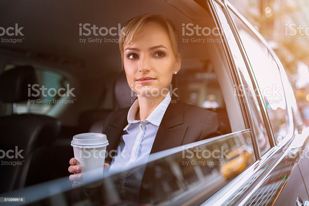 Businesswoman traveling though city in car stock photo