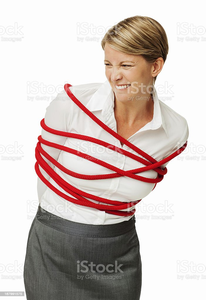 Businesswoman Trying To Set Herself Free From Rope stock photo