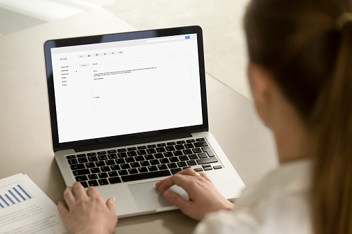 istock Businesswoman typing corporate e-mail using laptop at office des 855752984