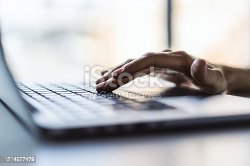 Businesswoman typing on laptop keyboard in sunny office, business and technology concept. Close up