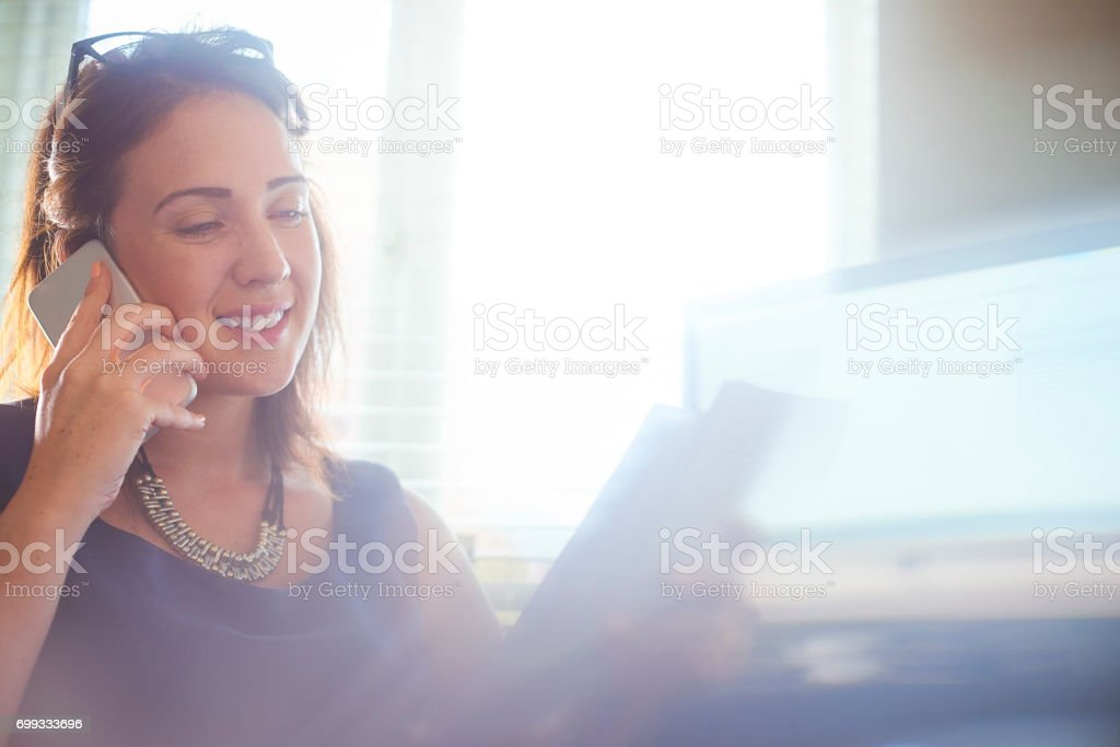 Businesswoman updating client on the phone stock photo