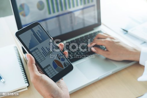 istock Businesswoman use computer and mobile phone to analyse online information. 807518724