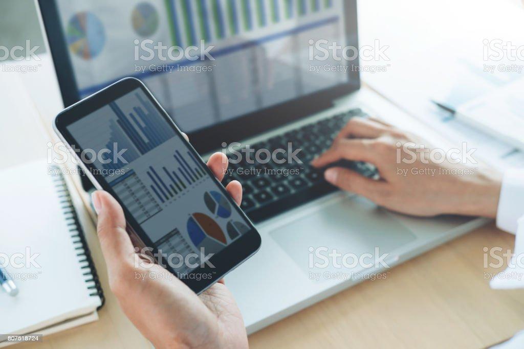 Geschäftsfrau verwenden Computer und Handy, um Online-Informationen zu analysieren. – Foto