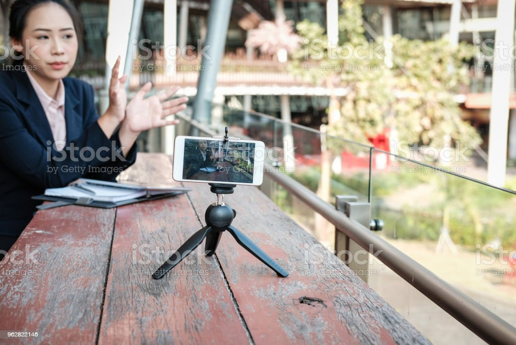 businesswoman use smartphone for online live streaming. woman recording video blog. vlogger presenting business vlog. - Foto stock royalty-free di Adulto