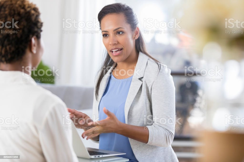 Businesswoman uses laptop while meeting with client stock photo