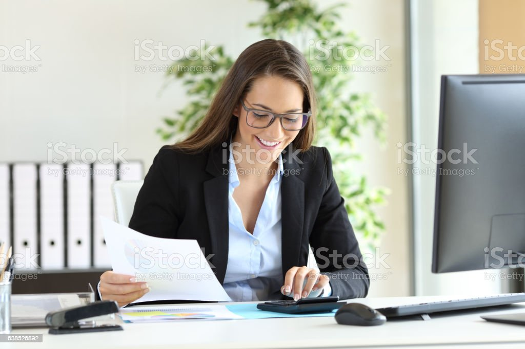 Businesswoman using a calculator at office stock photo