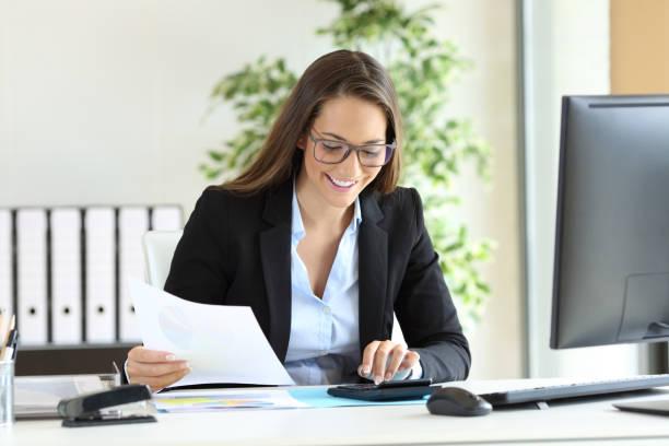 businesswoman using a calculator at office - gerente de cuentas fotografías e imágenes de stock