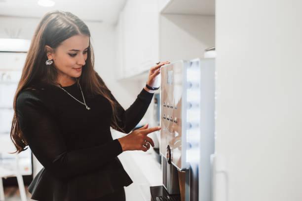 Businesswoman using a coffee machine indoors stock photo