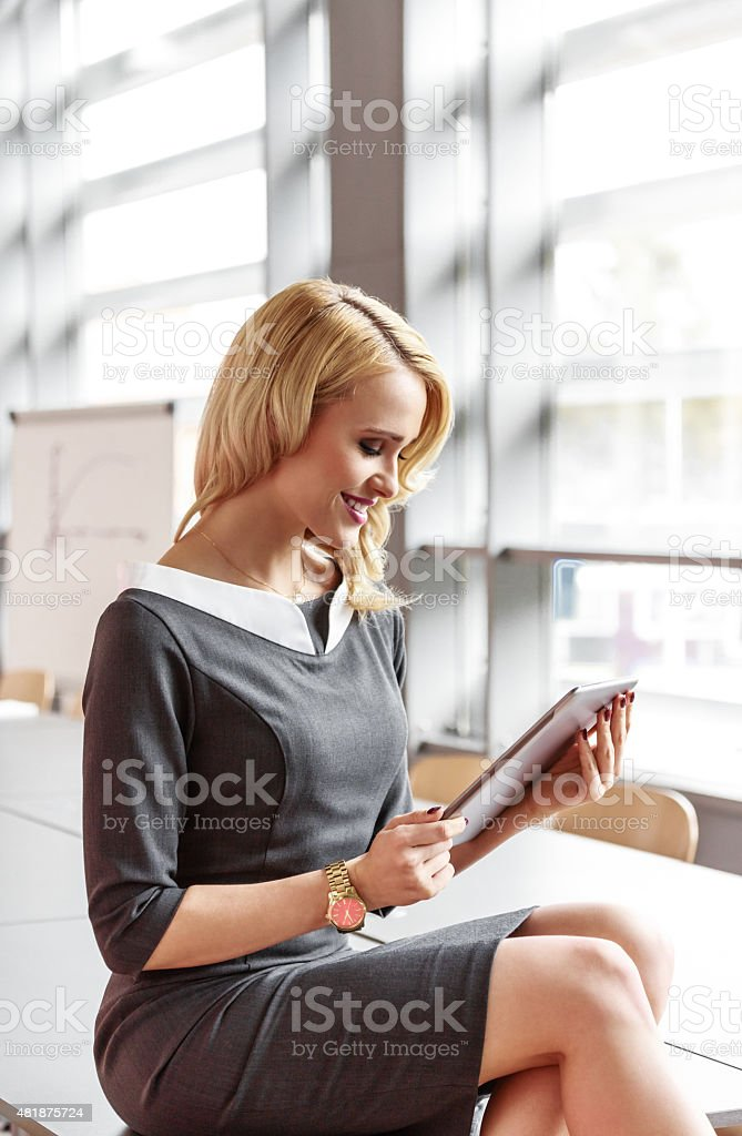 Businesswoman using a digital tablet in an office Portrait of beautiful blonde young businesswoman wearing grey dress sitting in a borad room in an office and using a digital tablet.  2015 Stock Photo