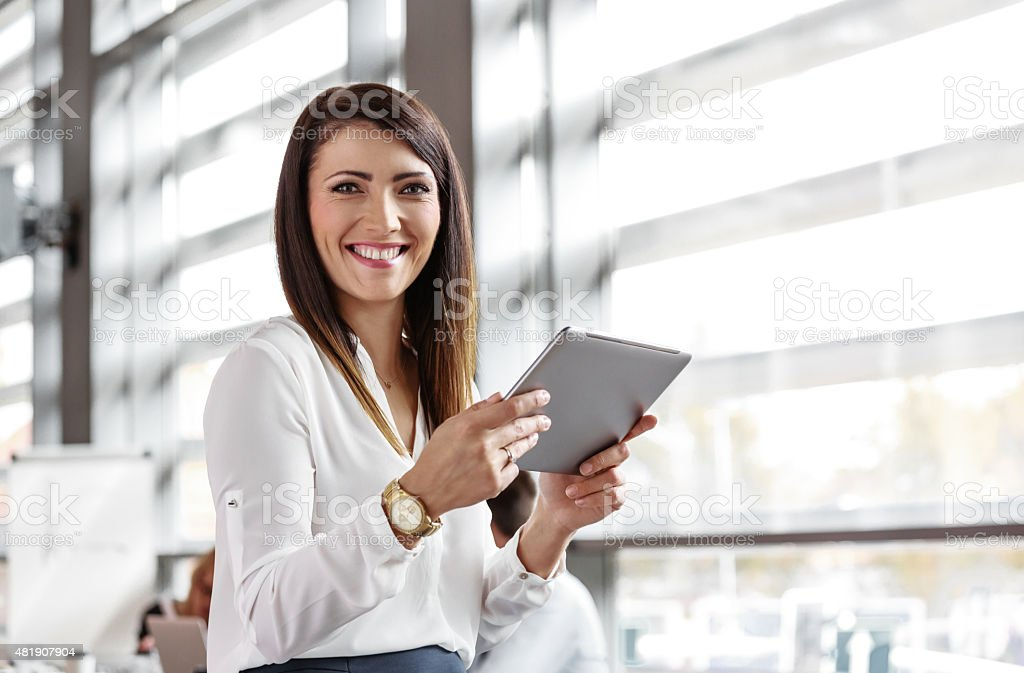 Businesswoman using a digital tablet in an office Friendly businesswoman wearing white shirt sitting in a board room in an office, holding a digital tablet in hands and smiling at camera.  2015 Stock Photo
