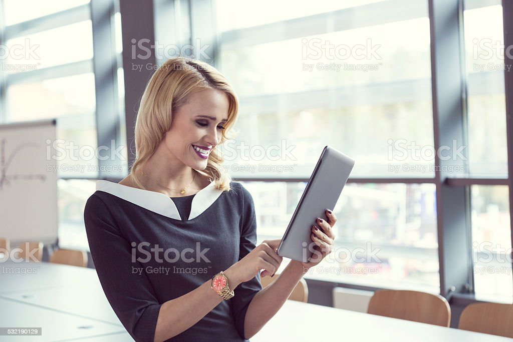 Businesswoman using a digital tablet in an office Smiling businesswoman using a digital tablet in a board room. 2015 Stock Photo
