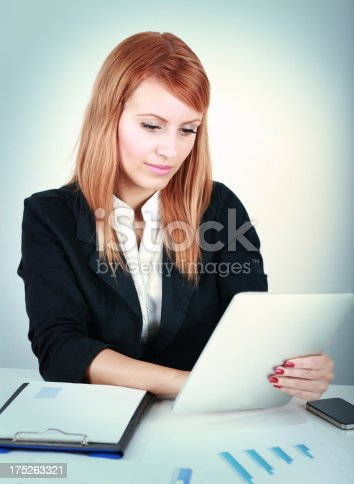 istock Businesswoman using a digital tablet in the office 175263321