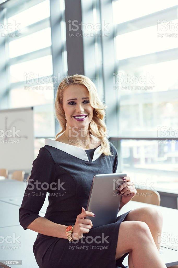 Businesswoman using a digital tablet Portrait of beautiful blonde young businesswoman wearing grey dress sitting in a borad room in an office and holding a digital tablet in hands, smiling at the camera. 2015 Stock Photo