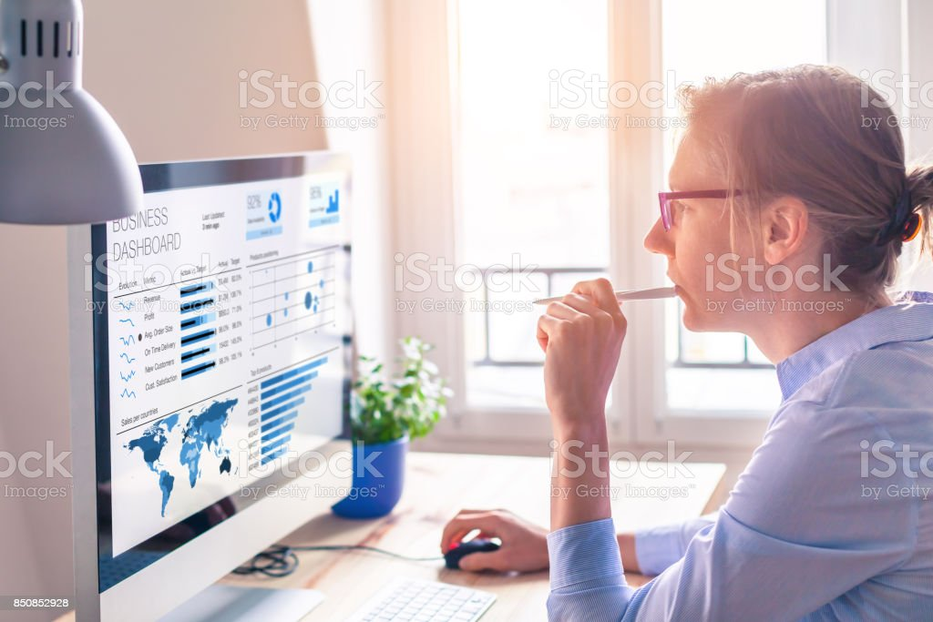 Businesswoman using business analytics or intelligence dashboard on computer screen stock photo