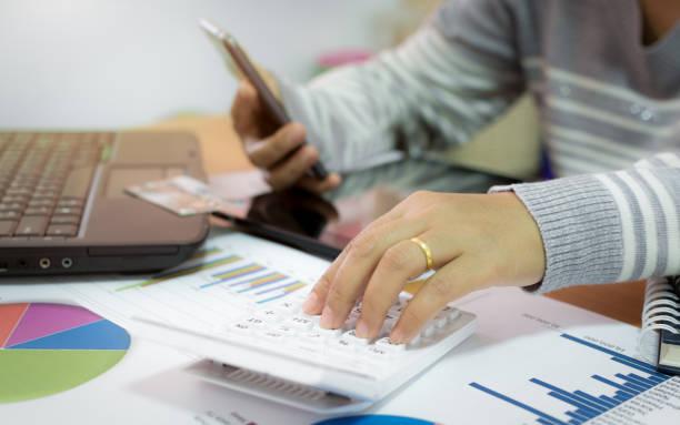 Femme d'affaires à l'aide de la calculatrice et exploitation mobile phone. - Photo