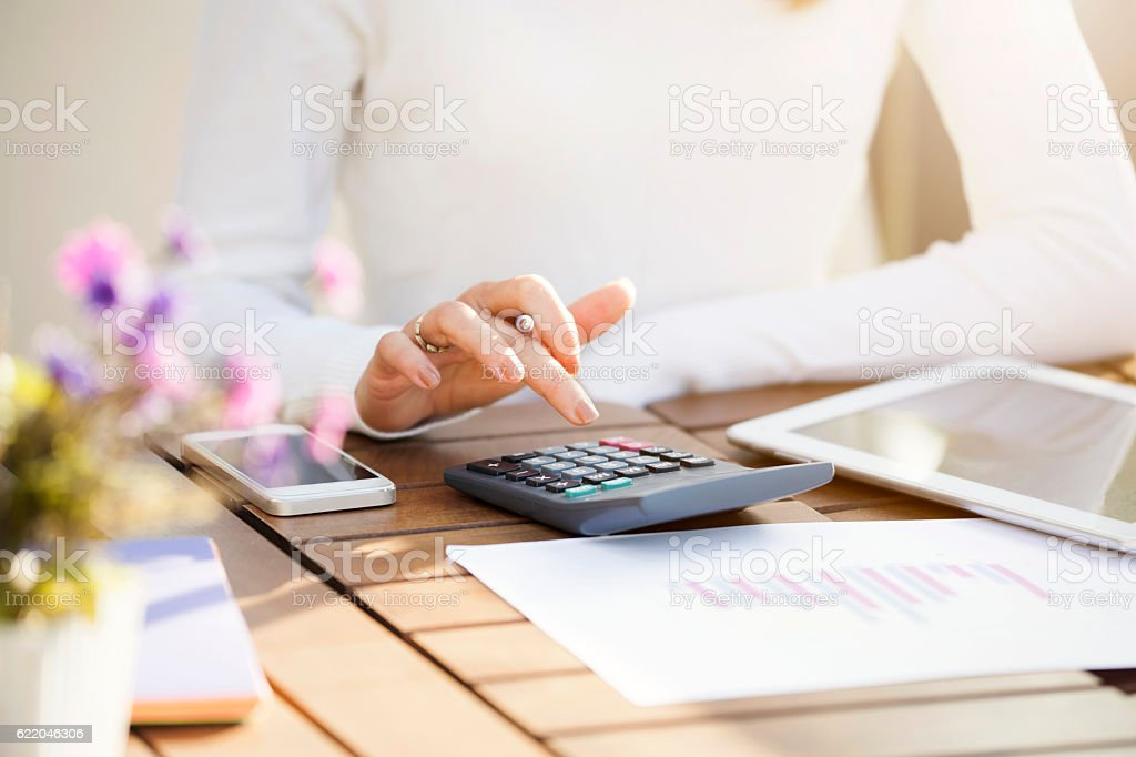 Businesswoman using calculator​​​ foto
