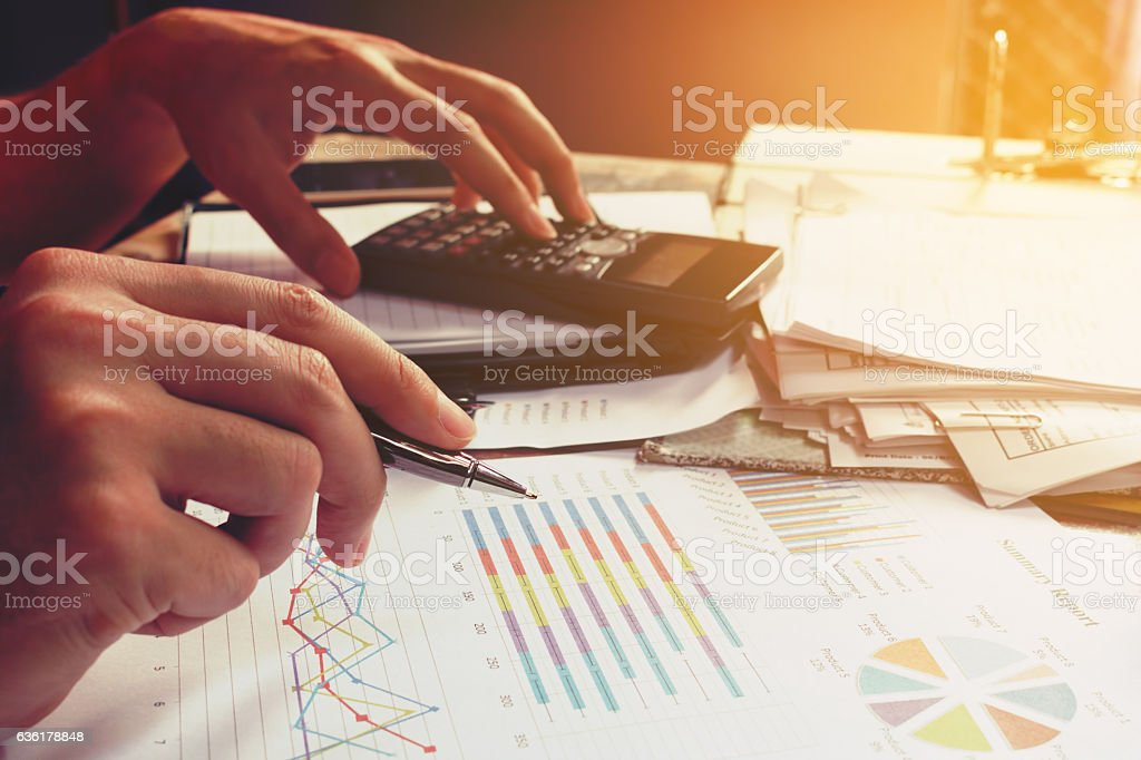Businesswoman using calculator with holding pen and thinking abo stock photo