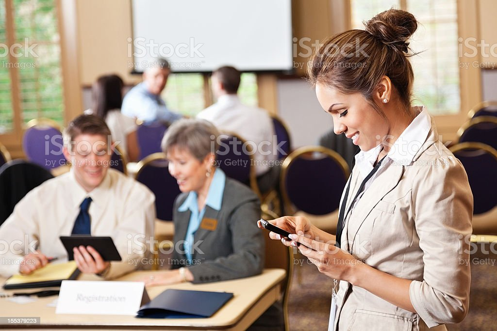 Businesswoman using cell phone at conference entrance royalty-free stock photo