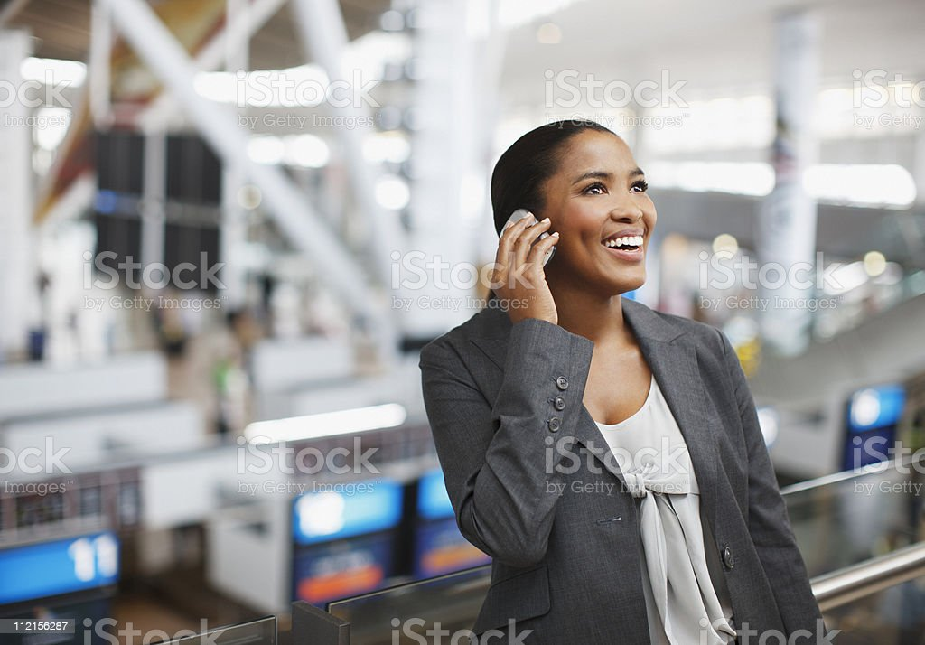 Businesswoman using cell phone in airport royalty-free stock photo