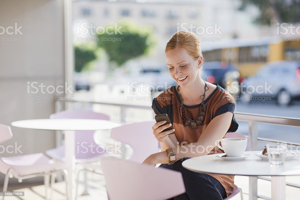 Businesswoman using cell phone in cafe royalty-free stock photo
