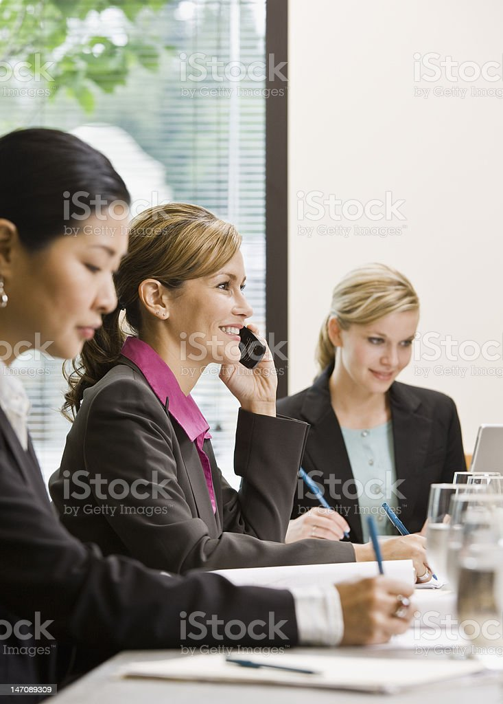 Businesswoman Using Cell Phone in Meeting royalty-free stock photo