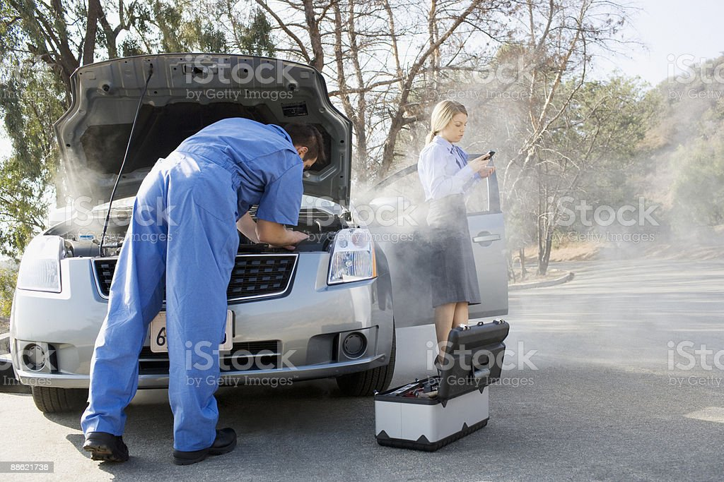 Businesswoman using cell phone while mechanic looks at car engine stock photo
