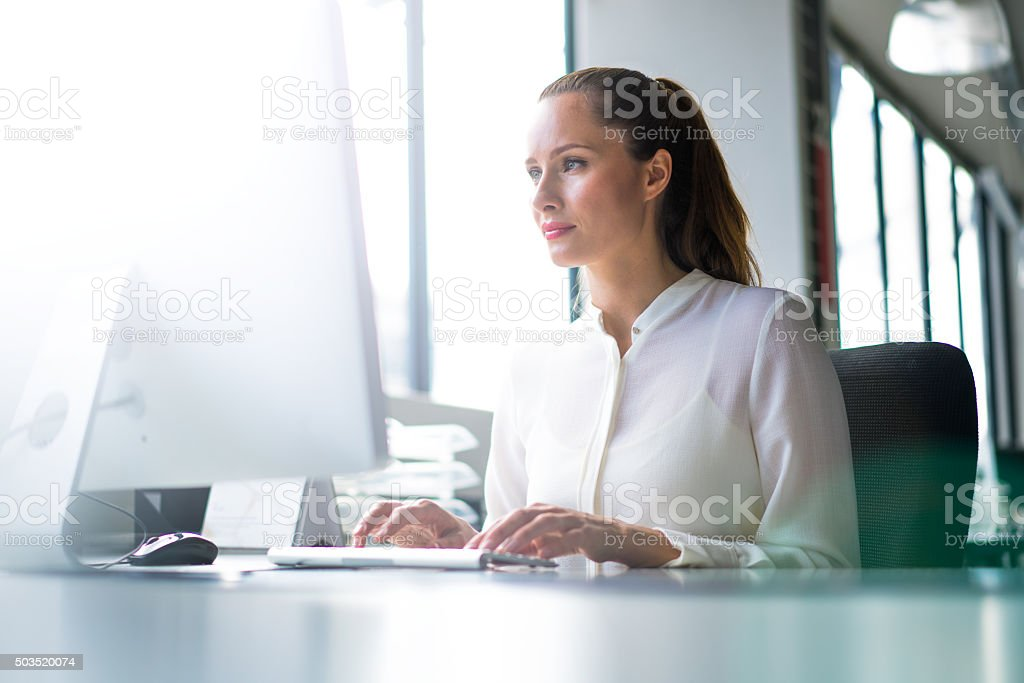 A photo of young businesswoman using computer at desk. Concentrated...