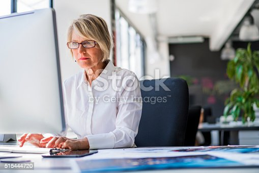 A photo of mature businesswoman using computer at desk. Concentrated female executive is working on desktop PC. Confident female professional is in formals. She is in brightly lit office.