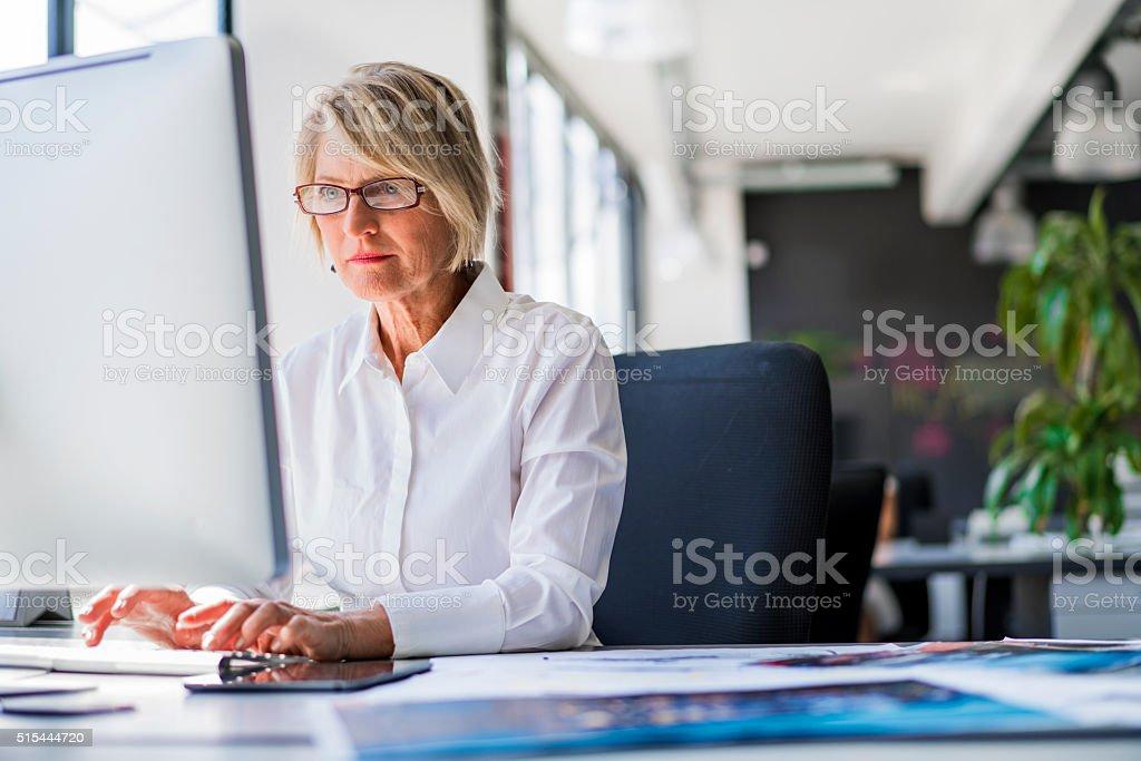 Empresaria usando la computadora en escritorio de oficina - foto de stock