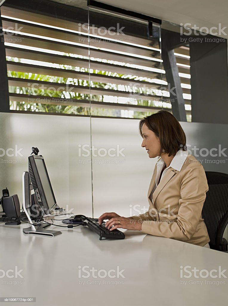 Businesswoman using computer at desk royalty free stockfoto