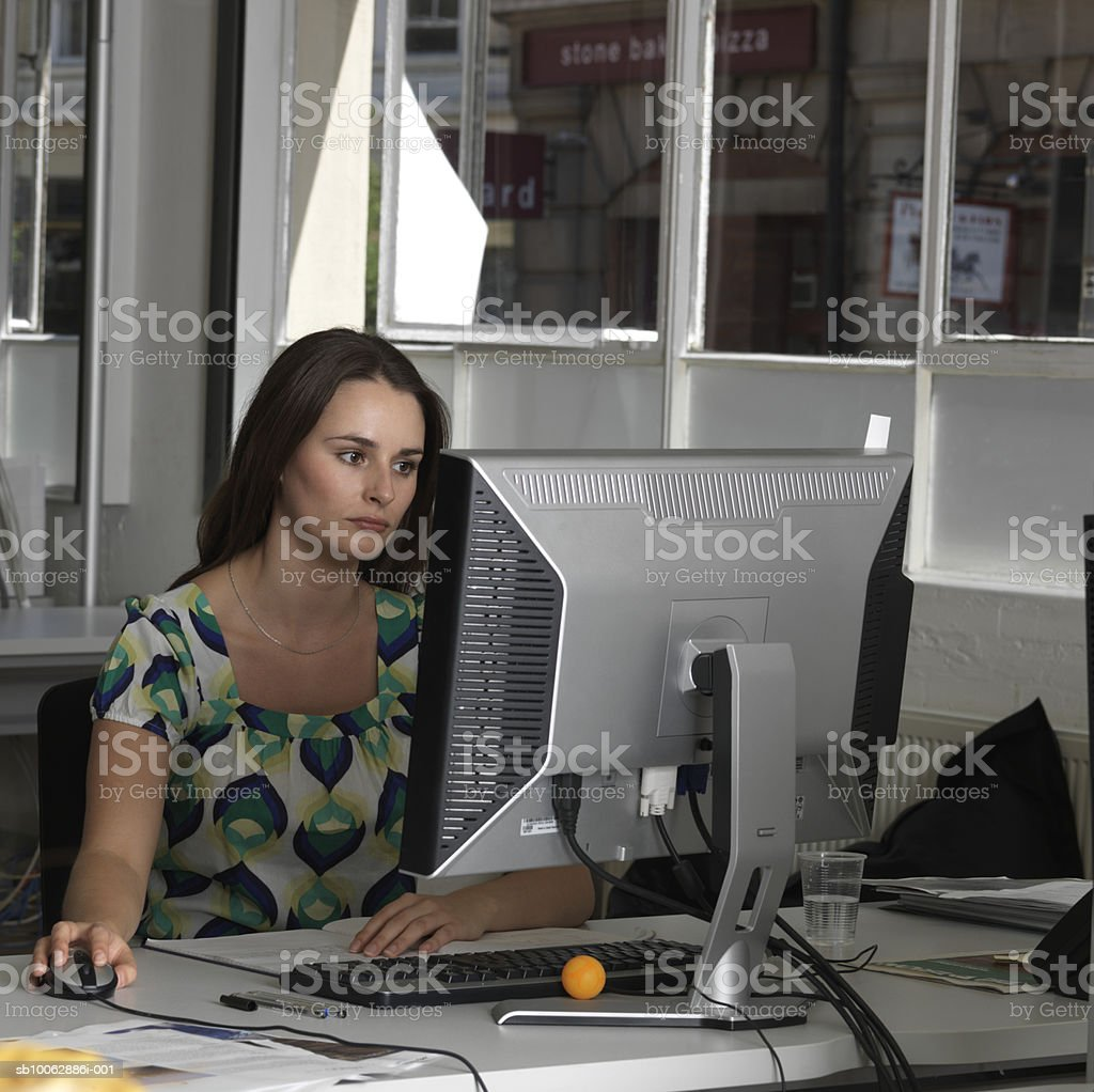 Businesswoman using computer at office desk foto de stock libre de derechos