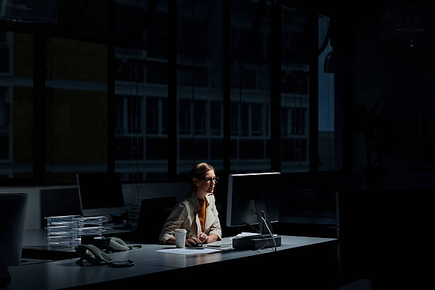 businesswoman using computer in dark office - être seul photos et images de collection