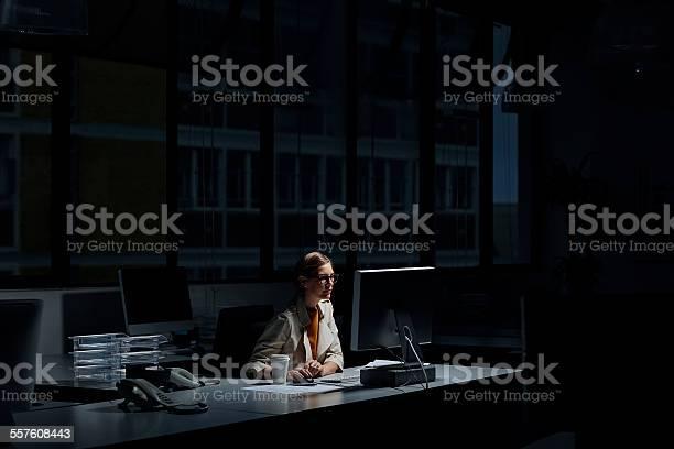 Photo of Businesswoman using computer in dark office