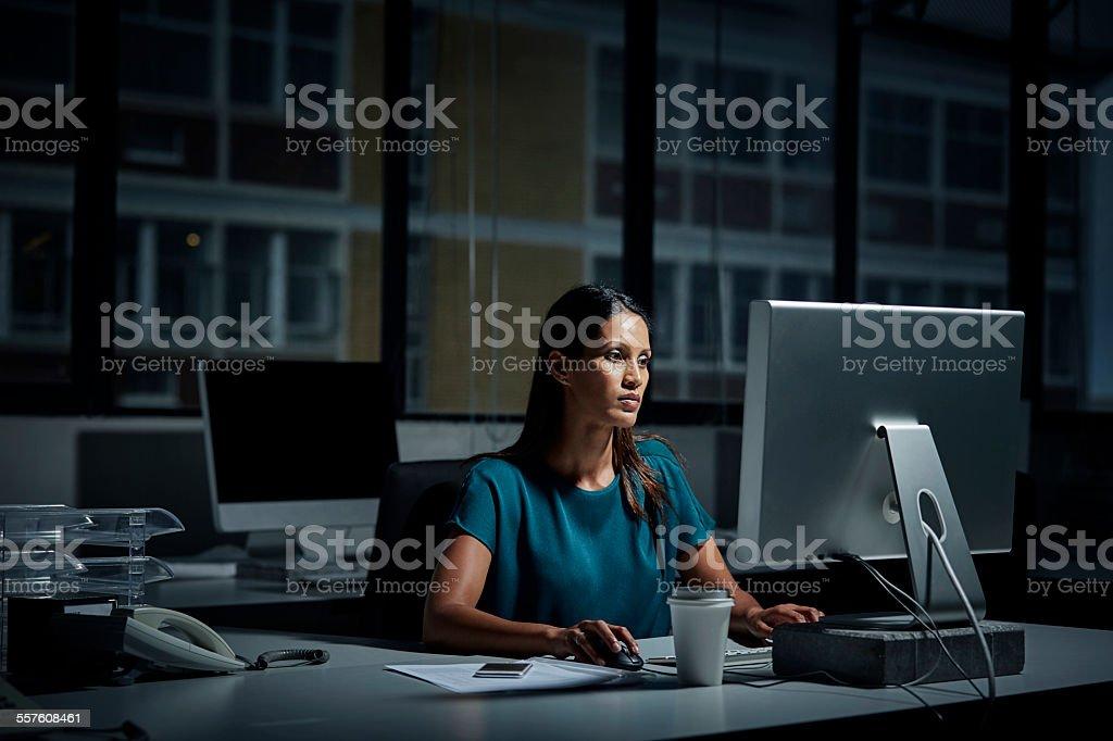 Businesswoman using computer in dark office stock photo