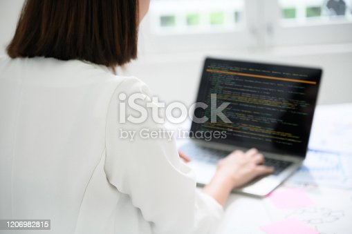Businesswoman using computer laptop in office room with paperwork document on desk. Programmers are working as software developers or web sites