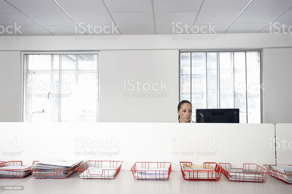 Businesswoman Using Computer With Trays Of Documents On Table stock photo