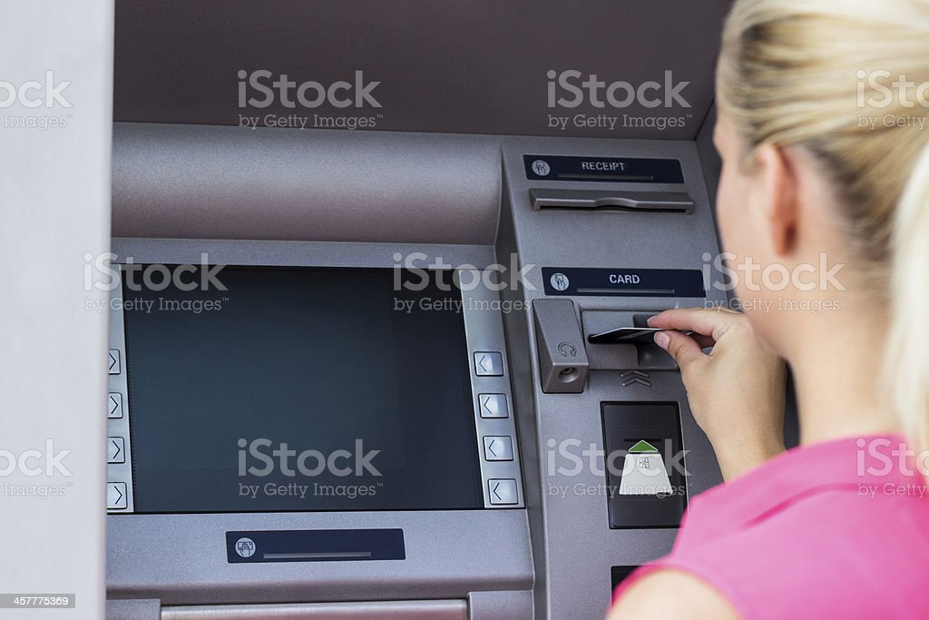 Businesswoman using credit card at an ATM royalty-free stock photo