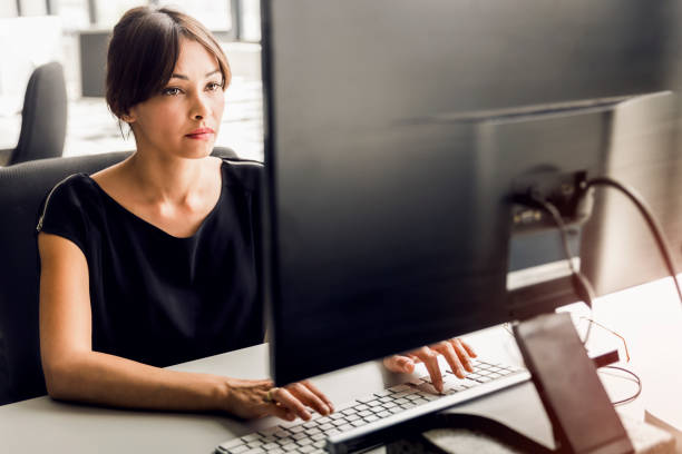 businesswoman using desktop pc at office - typing stock photos and pictures