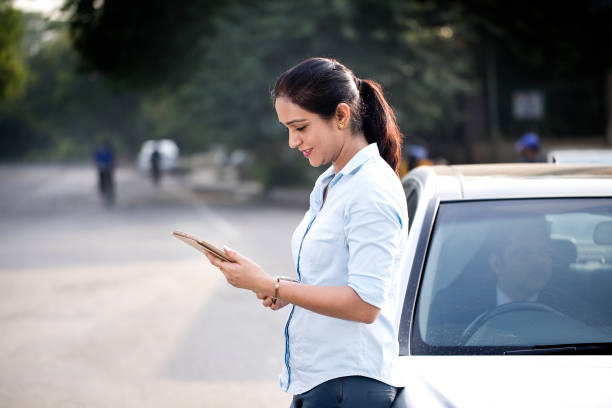 Businesswoman using digital tablet leaning on car in city stock photo