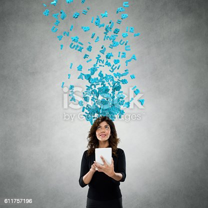 istock Businesswoman using digital tablet with flying alphabets 611757196