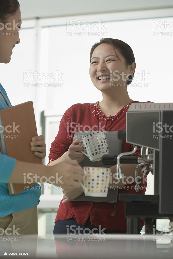 Businesswoman using espresso coffee machine and taking with her colleague in cafeteria royalty-free 스톡 사진