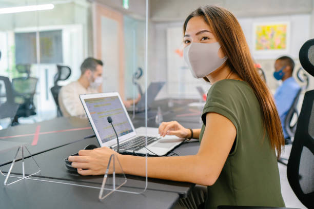 Businesswoman using headset and working on laptop in office while wearing protective face mask stock photo