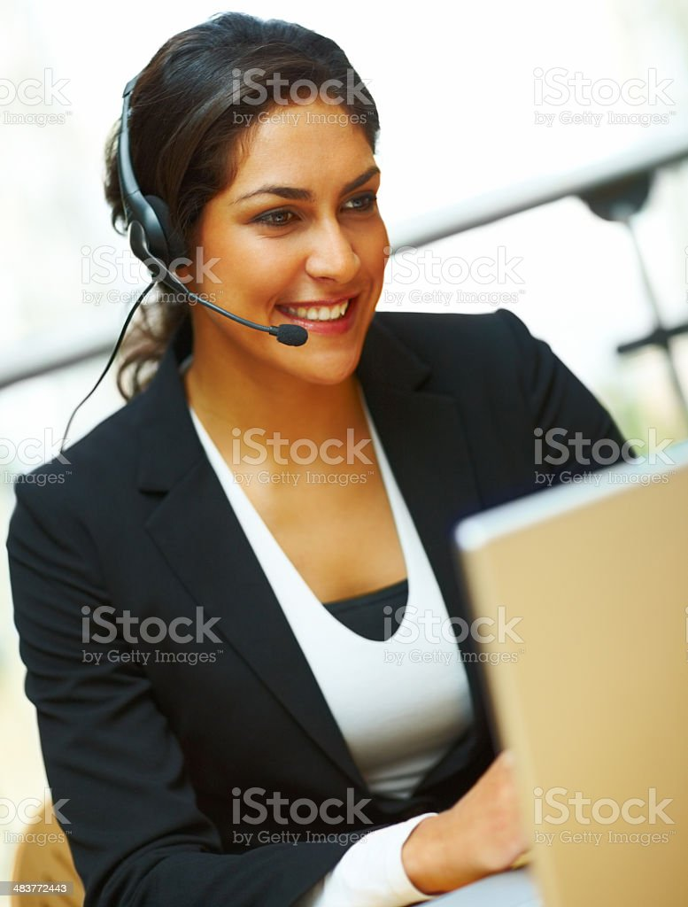 Businesswoman using headset and working on laptop royalty-free stock photo