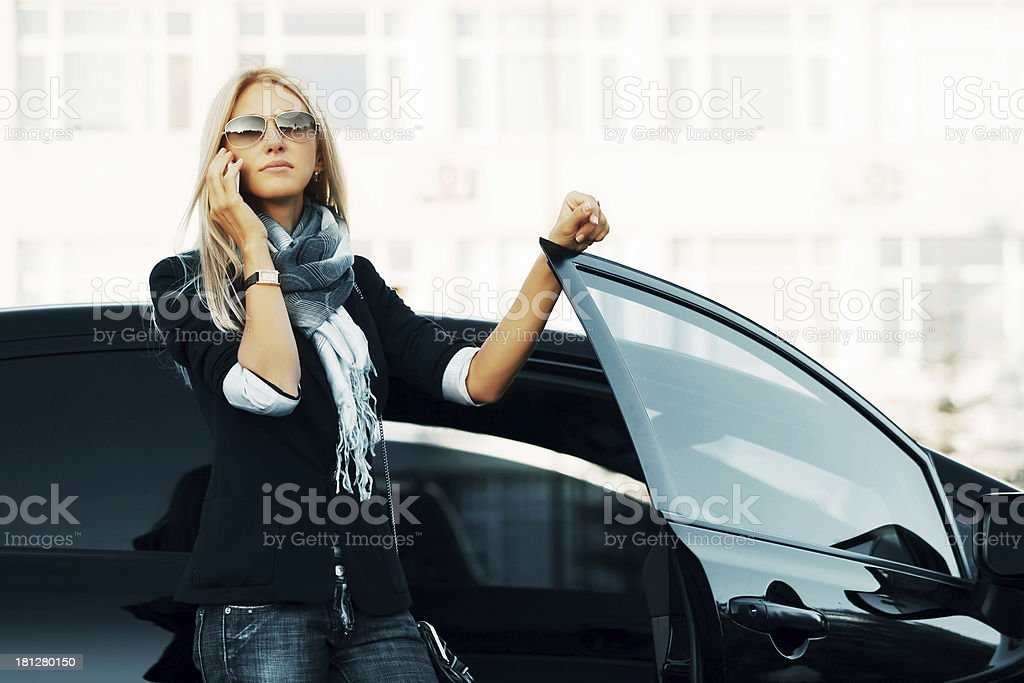 A businesswoman using her cellphone outside a car stock photo
