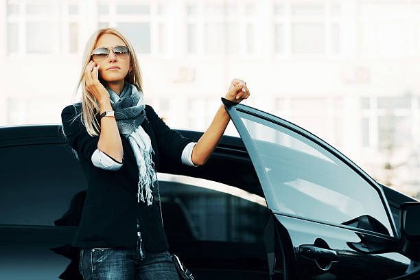 A businesswoman using her cellphone outside a car