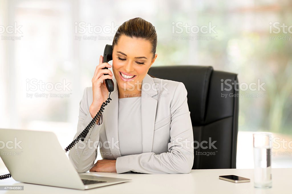 businesswoman using landline phone stock photo